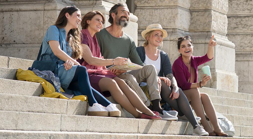 Familie sitzt mit Kompressionsstrümpfen auf Stufen