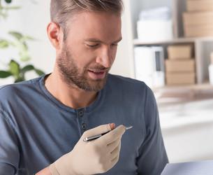Mann mit Juzo ScarPrime Seamless Handschuh hält Stift in der Hand