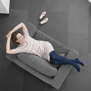 Kvinna med Juzo kompressionsstrumpor på en säng