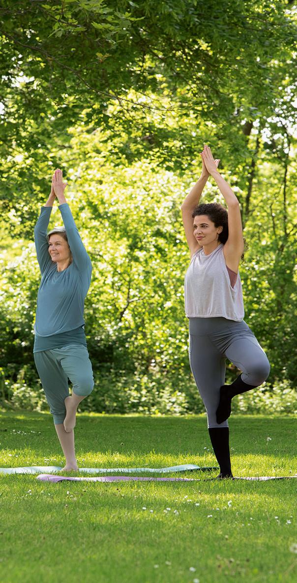 Femmes pratiquant le yoga dans le parc avec Juzo Move