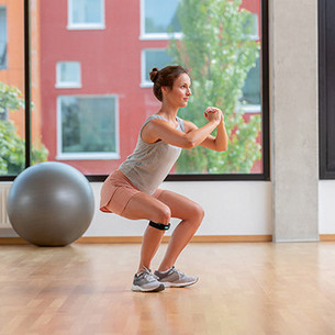A woman doing squats with arms in front of her chest