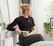 Frau mit schwarzer Thorax-Bandage sitzt an einem Frisiertisch und hält eine Tasse Tee