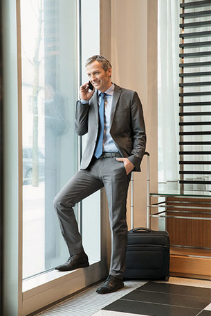 Man in business outfit is standing at the window