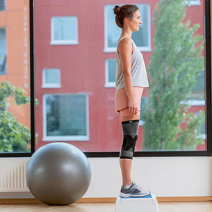 A woman standing on an aerobics step with both legs