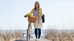 Woman with compression stockings is pushing her bike.