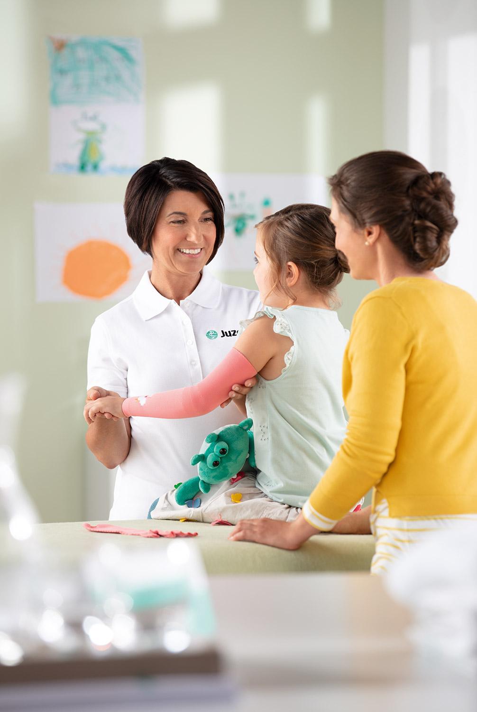Frau im Sanitätshaus begutachtet Mädchen mit Narben