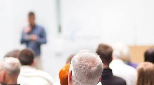 Personen sitzen im einem Vortrag