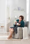 Donna beve tè in poltrona indossando la calza Juzo Ulcer Pro