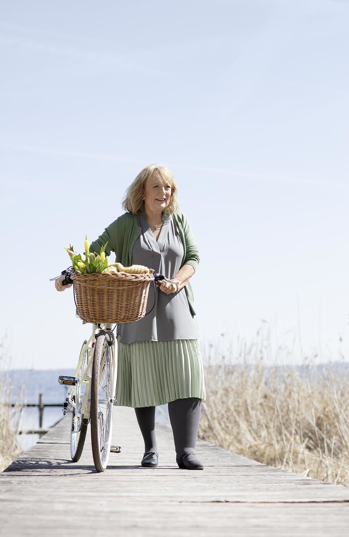 Frau mit Fahrrad trägt Juzo Kompressionsstrümpfe