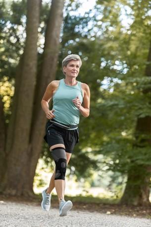 Frau im Wald beim Joggen mit Patella Xtex Plus Bandage
