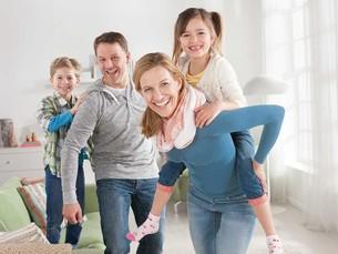 Foto einer Familie im Wohnzimmer auf dem die Frau eine blaue Thoraxbandage trägt