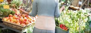 Kobieta w supermarkecie ma na sobie ortezę pleców